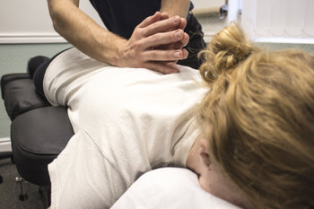 Our chiropractor providing manipulative therapy to female patient who has issues in the mid back