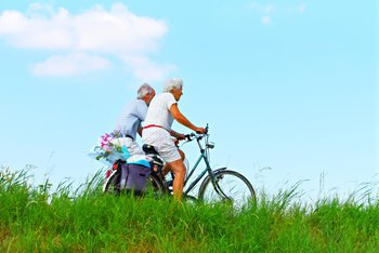 A happy elderly couple keep fit and healthy by riding bicycles while enjoying the great outdoors