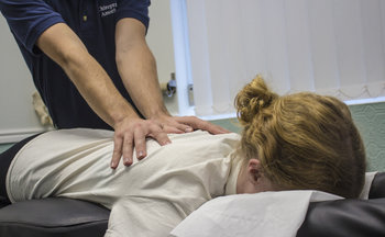 Preston chiropractor Jon Shurr providing treatment for female patient at Chiropractic Associates